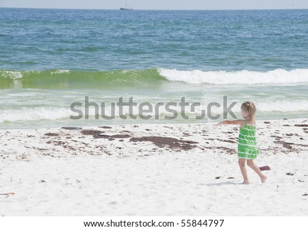 PENSACOLA BEACH - 23 JUNE: An unidentified young girl plays with sand by oil covered sand on June 23, 2010 in Pensacola Beach, FL. - stock photo