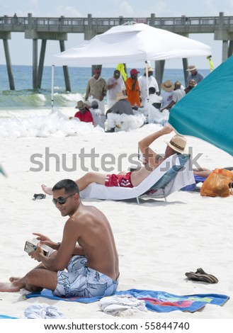 PENSACOLA BEACH - JUNE 23: Beachgoers rest on the beach on June 23, 2010 in Pensacola Beach, FL. BP oil workers are seen in the background. - stock photo