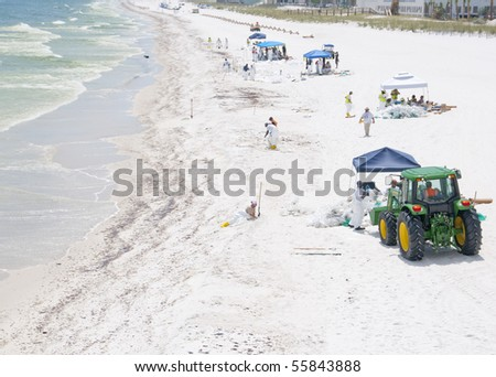 PENSACOLA BEACH - JUNE 23:  BP oil workers attempt to clean oil covered sand on June 23,  2010 in Pensacola Beach, FL. 	 - stock photo