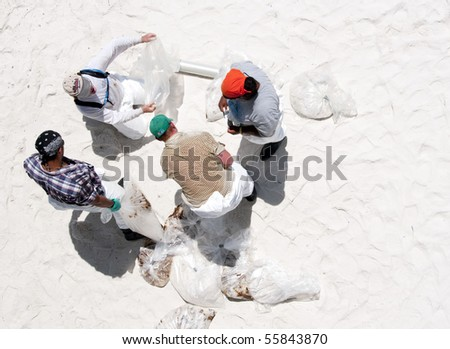 PENSACOLA BEACH - JUNE 23:  BP oil workers bag oil covered sand on June 23, 2010 in Pensacola Beach, FL. - stock photo