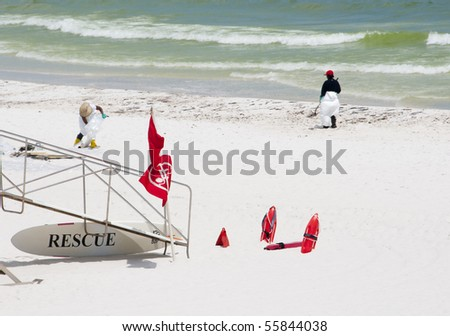 PENSACOLA BEACH - 23 JUNE:  BP oil workers clean oil near a lifeguard stand on June 23, 2010 in Pensacola Beach, FL. - stock photo