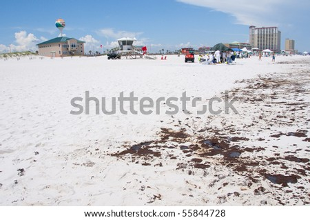 PENSACOLA BEACH - 23 JUNE: Oil lies near the Pensacola Beach, FL pier on June 23, 2010 as tourists stay away from the resort beach at the height of the summer season. BP workers in the distance. - stock photo
