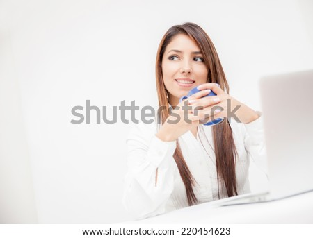 Pensinve businesswoman drinking coffee in her desk - stock photo
