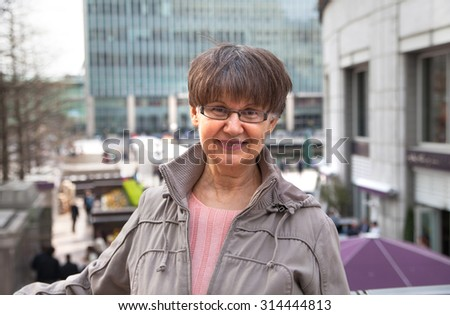 Pension age good looking woman portrait in the City. London - stock photo