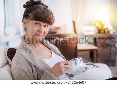 Pension age good looking woman with cup of tea - stock photo