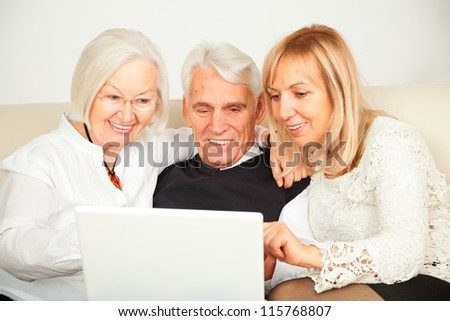 pensioner couple and daughter with computer - stock photo