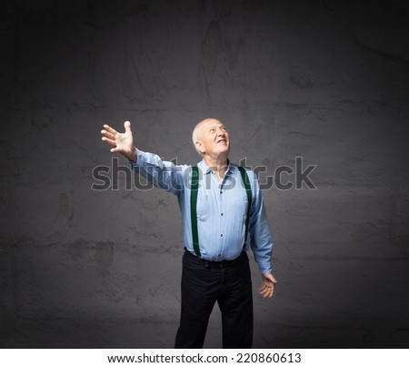pensioner showing empty space with open arm - stock photo