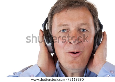Pensioner with headphones singing happy to mp3 music. Isolated on white background. - stock photo
