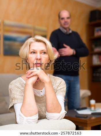 Pensioners couple are having a quarrel. Mature wife is sitting turned away from her old husband with her arms near her cheek and the husband is standing behind and talking to her - stock photo