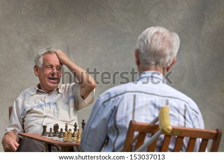 Pensioners playing chess in courtyard - stock photo