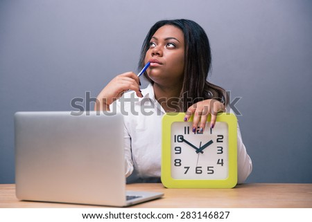 Pensive african american businesswoman sitting at the table with pen and laptop in office over gray background - stock photo