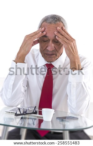 Pensive and Frustrated middle aged businessman sitting at office desk in front of a coffee - stock photo