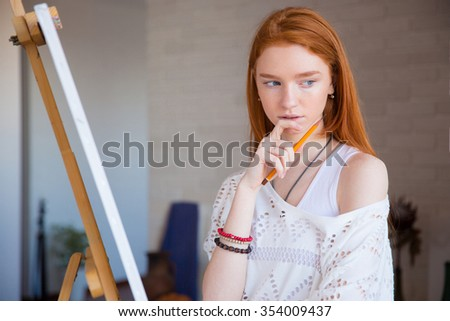 Pensive attractive young female artist with red hair standing and thinking near easel in drawing class - stock photo