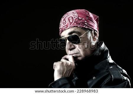 Pensive biker with leather jacket, sunglasses and bandana - stock photo