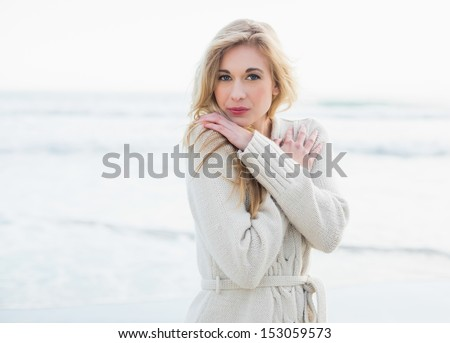 Pensive blonde woman in wool cardigan looking at camera on the beach - stock photo