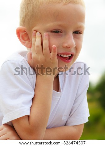 Pensive boy child thinking and daydreaming. Thoughtful kid leaning on his hand looking forward. Imagination. - stock photo