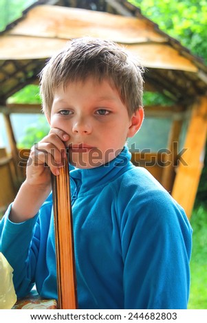 Pensive boy in the summer of wooden gazebo - stock photo