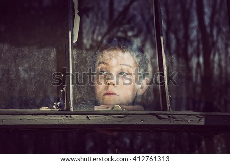 Pensive boy looking out an old dirty window - stock photo