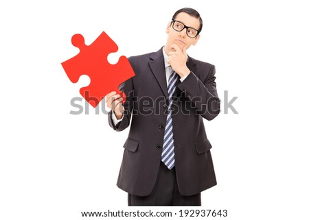 Pensive businessman holding a piece of puzzle isolated on white background - stock photo