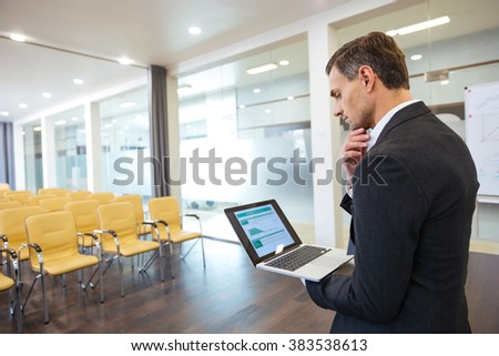 Pensive businessman looking on financial report on the screen of laptop standing in empty conference hall - stock photo