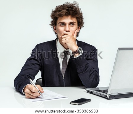 Pensive businessman looking up with concentration and writing in his paperwork at office on gray background / depression and crisis concept - stock photo