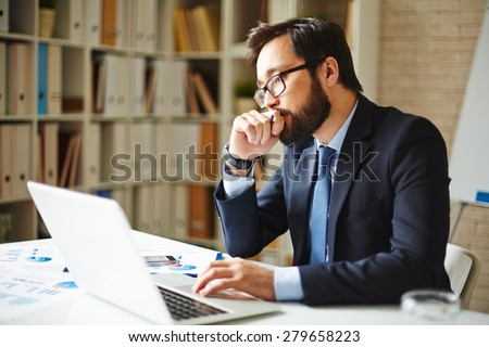 Pensive businessman sitting in front of laptop in office - stock photo