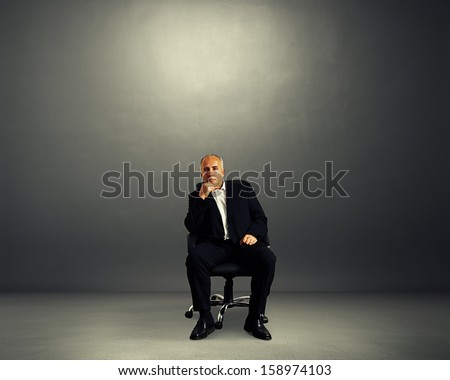 pensive businessman sitting on office chair and looking at camera - stock photo
