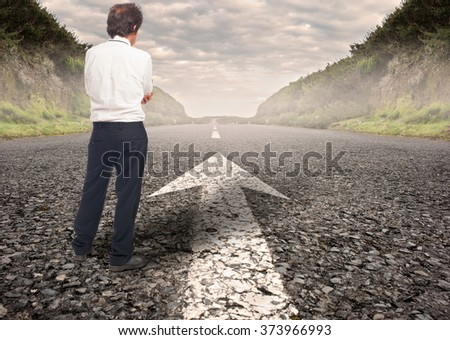 pensive businessman standing on a road - stock photo