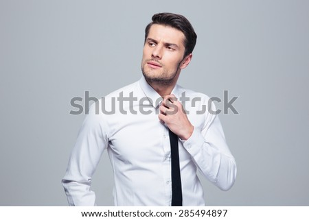 Pensive businessman straightening his tie over gray background. Looking away - stock photo