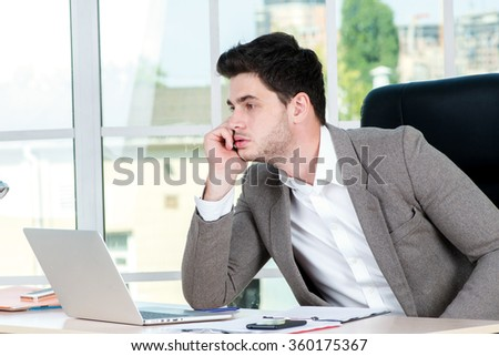 Pensive businessman. Successful confident businessman sitting in office at the table and working on a laptop while young businessman in formal attire thinking on the problem - stock photo