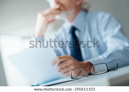Pensive businessman with hand on chin looking away and holding a document, selective focus, glasses on foreground - stock photo