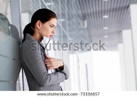 Pensive businesswoman with documents by wall - stock photo