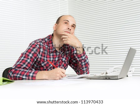 pensive casual man sitting at table with a laptop computer - stock photo