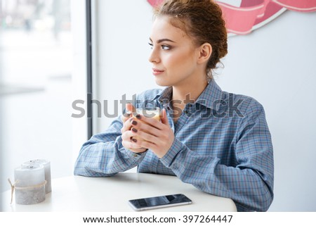 Pensive charming young woman drinking coffee in cafe - stock photo