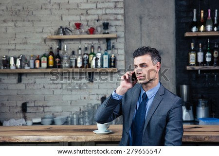 Pensive confident businessman talking on the phone in cafe and looking away - stock photo
