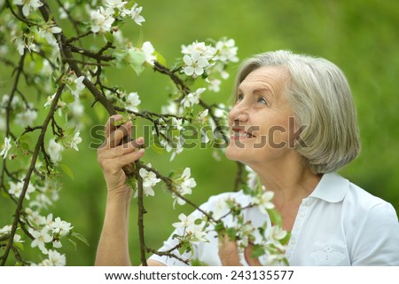 Pensive elderly woman walking in the spring nature with cherry flowers - stock photo