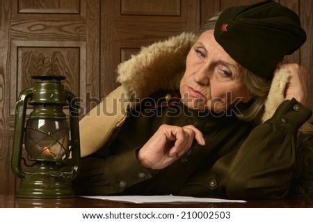 Pensive elderly woman writes a letter to a soldier home - stock photo