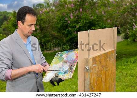 Pensive fashionable middle-aged artist holding a palette standing in front of a sketchbook during an art class in a forest - stock photo