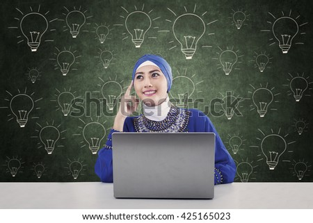 Pensive female muslimah sitting in class with hand drawn lightbulb - stock photo