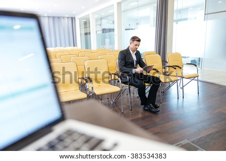 Pensive focused businessman sitting and using tablet in empty conference hall - stock photo