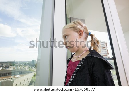 Pensive girl in vampire costume looking out through window at home - stock photo