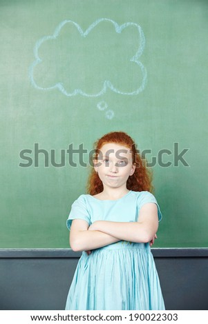 Pensive girl with thought bubble in chalkboard in elementary school - stock photo