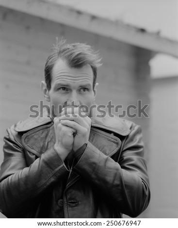 Pensive guy portrait. Trench coat. Outdoor shoot - stock photo