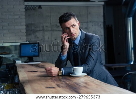 Pensive handsome businessman talking on the phone in cafe and looking away - stock photo