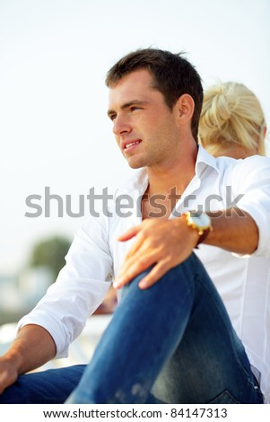 Pensive handsome man looking aside outdoors with his girlfriend sitting behind - stock photo