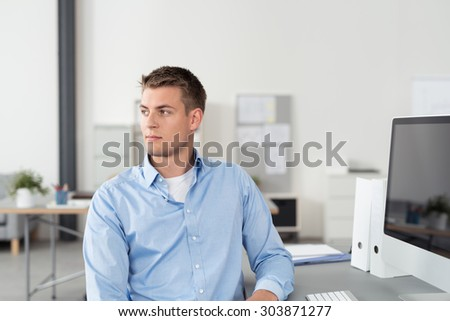 Pensive Handsome Young Businessman Sitting at his Worktable Inside the Office, Looking Into Distance. - stock photo