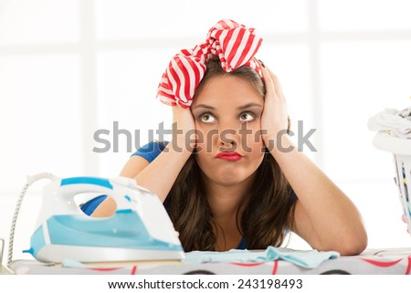 Pensive housewife daydreaming leaning on an ironing board holding her head. In front of her are iron and laundry basket. - stock photo