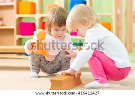 Pensive kids playing in kindergarten room - stock photo