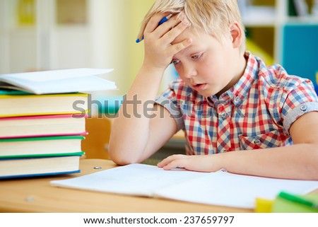 Pensive little boy concentrating on subject of lesson - stock photo