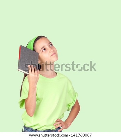 Pensive little girl with headband and a book isolated on green background - stock photo